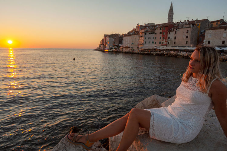 Woman sitting on sea shore against sky during sunset