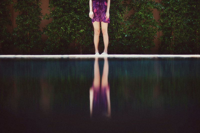 Low section of woman standing by swimming pool against trees