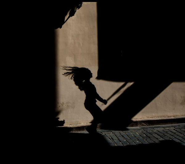 Silhouette of boy walking on staircase