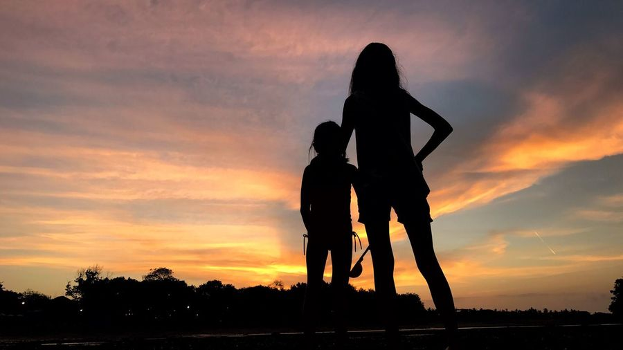 Silhouette woman with girl against sky during sunset