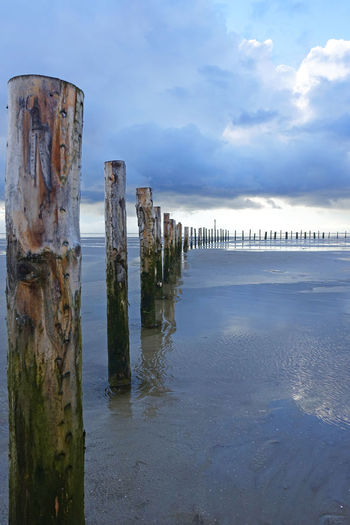 St. Peter Ording Mudflat Wadden Sea Clouds And Sky Wooden Stake Wooden Stakes Wooden Stakes On Beach