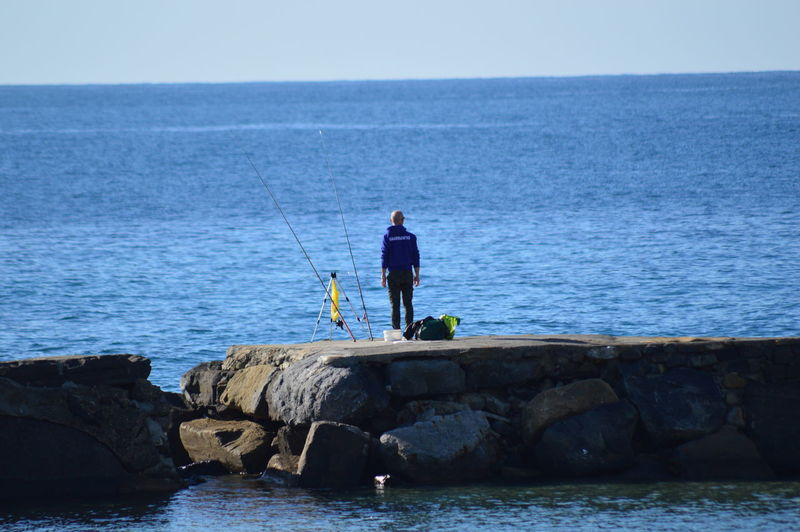 Man fishing on rock by sea against sky