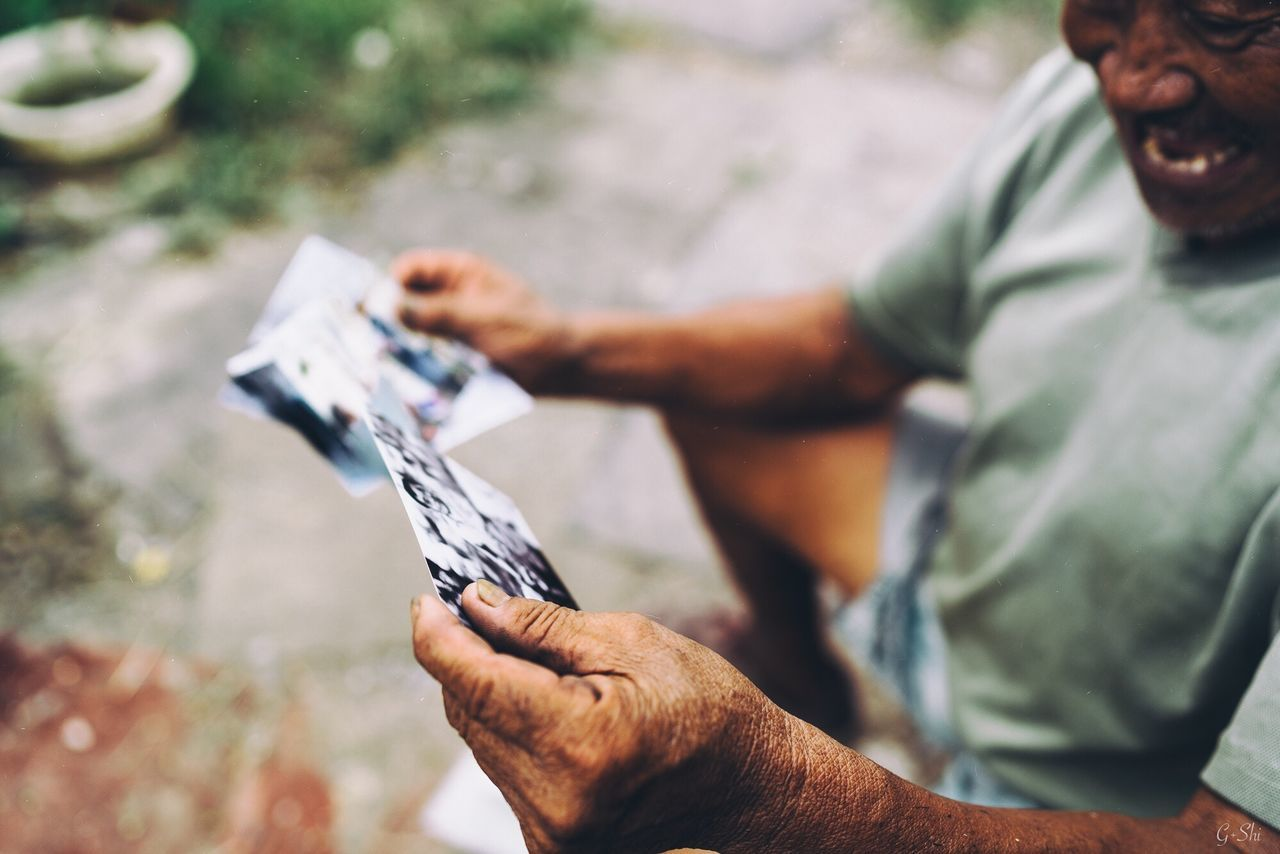 High angle view of senior man holding photographs while sitting outdoors