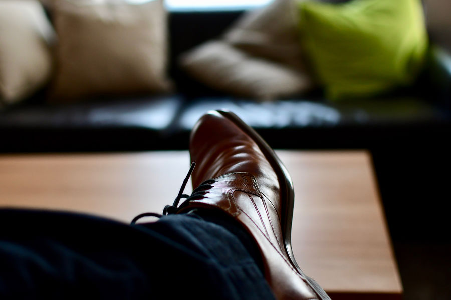 Business Adult Body Part End Of Working Day Furniture Home Interior Human Body Part Human Foot Human Leg Indoors  Jeans Leather Leisure Activity Lifestyles Low Section Men One Person Personal Perspective Real People Relaxation Selective Focus Shoe Shoes Sitting