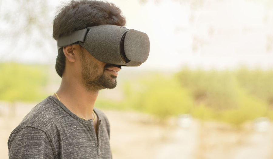 Side view of smiling man wearing virtual reality simulator at home