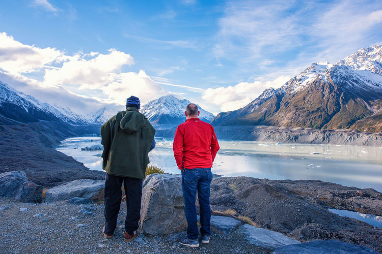 Brothers Beauty In Nature Brothers Cloud - Sky Full Length Leisure Activity Lifestyles Men Mountain Mountain Range Nature Non-urban Scene Outdoors People Real People Rear View Scenics - Nature Sky Snow Snowcapped Mountain Togetherness Two People Water Winter