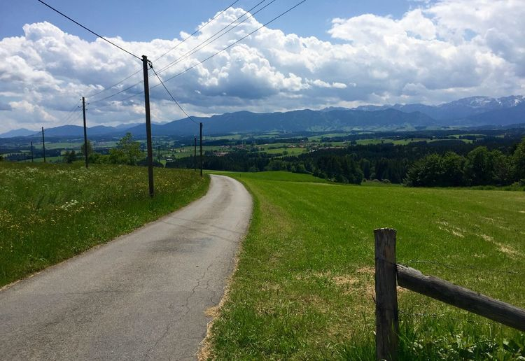 Country Road Passing Through Grassy Field