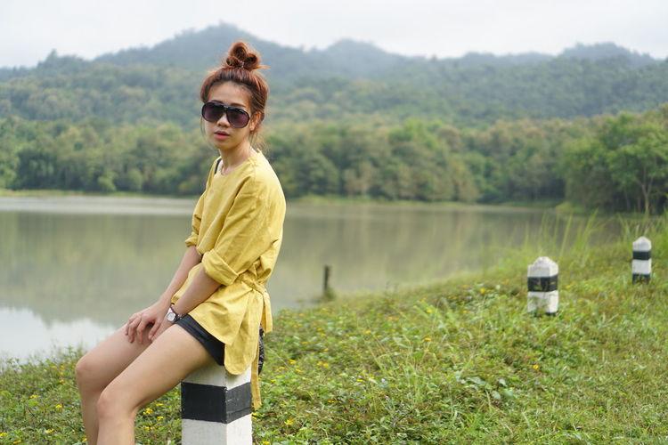 Portrait Of Woman Wearing Sunglasses While Sitting On Bollard At Lakeshore