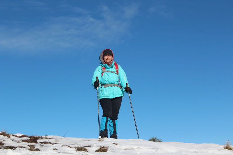 Woman with hiking poles standing in snow against blue sky