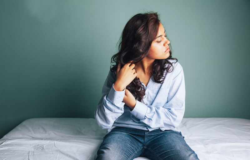 A young girl in a blue shirt. Girl In Blue Shirt Girl Wearing Shirt In Bed Girl In Bed Girl Playing With Hair Long Hair Beautiful Woman Heart Shaped Lips, A Go  Girl In Denims Girl Sitting Against A Wall.