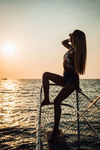 Water Sea Sky Beauty In Nature Sunset One Person Real People Lifestyles Sitting Leisure Activity Scenics - Nature Horizon Over Water Nature Women Horizon Young Adult Hairstyle Adult Hair Outdoors Looking At View