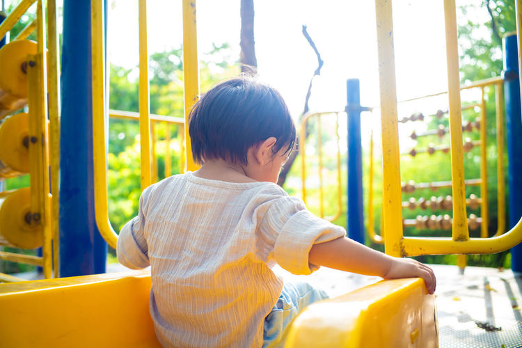 Rear view of boy sitting at playground