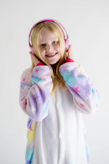 Portrait of happy girl listening music in headphones against white background