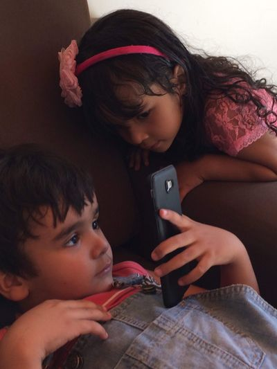 Girl looking at brother using smart phone while relaxing on sofa at home