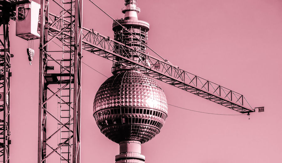 Construction Fernsehturm Pink Red Architecture Building Exterior Built Structure City Communication Crane Crane - Construction Machinery Day Electricity  Electricity Pylon Low Angle View No People Outdoors Sky Skyscraper Tall - High Technology Television Tower Tower Travel Destinations Rethink Things