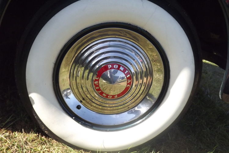 Closeup of a shiny vintage Pontiac whitewall tire and hubcap Hubcap Pontiac Reflection Circle Close-up Display Field No People Outside Sky Tire Vintage Whitewalls