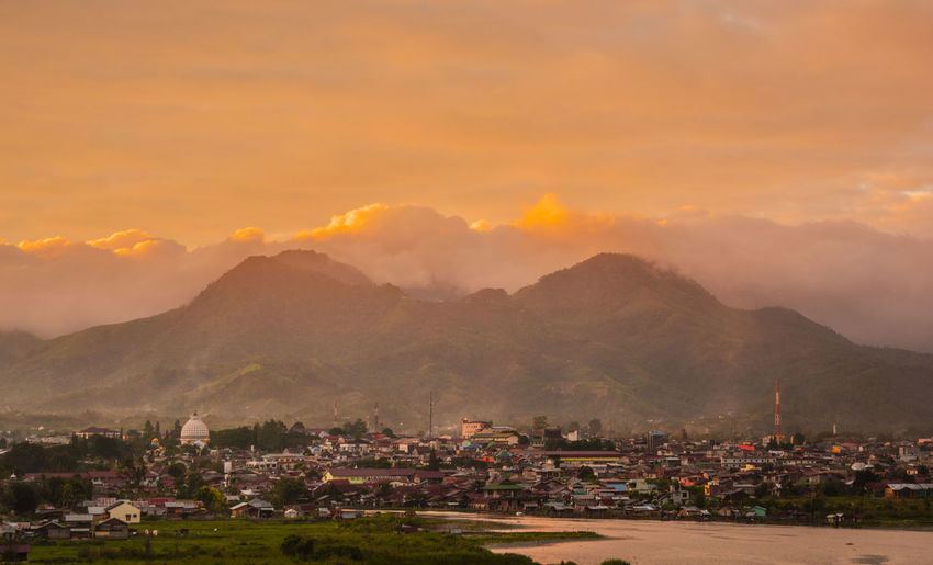 Scenic view of townscape by mountains against sky during sunset