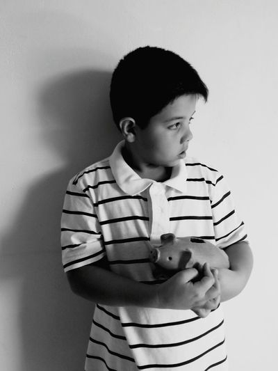Boy With Piggy Bank At Home