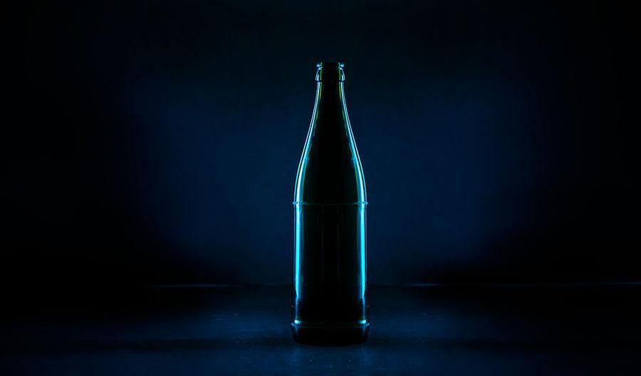 Close-up of illuminated bottle on table against black background