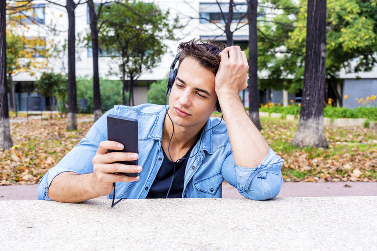 Man listening music while using mobile phone in city