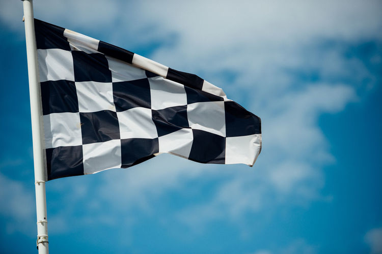 Blue Chequered Flag Close-up Cloud Cloud - Sky Cloudy Culture Day Finish Finish Line  Focus On Foreground Low Angle View Modern Motorsport Multi Colored Nature No People Outdoors Part Of Pole Sky
