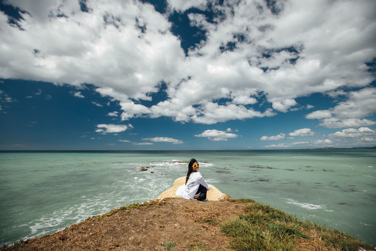 Woman sitting at beach against sky
