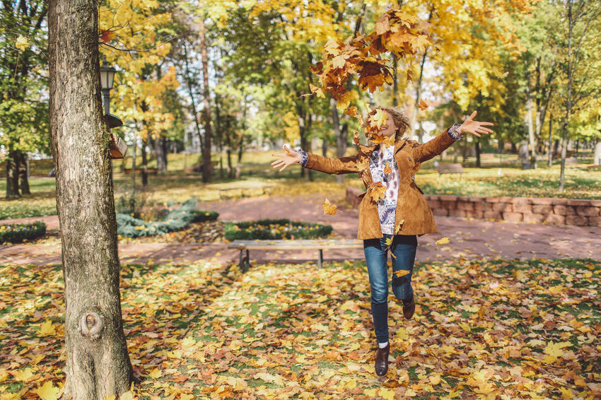 Adults Only Arms Raised Autumn Autumn Autumn Colors Autumn Leaves Carefree Colors Curly Hair Day Forest Full Length Girl Happiness Leaf Leafs Leisure Activity Nature Outdoors Park Rear View Sunlight Tree Trees Young Adult