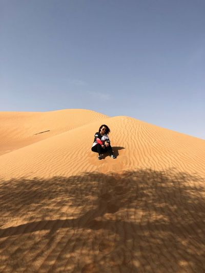 Low angle view of woman sitting on sand dune at desert against blue sky