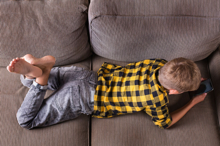 High angle view of boy sitting on sofa at home