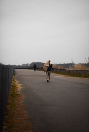 Rear view of man walking on road against clear sky