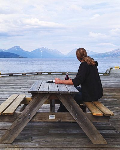 Man sitting on picnic table at pier in sea against sky