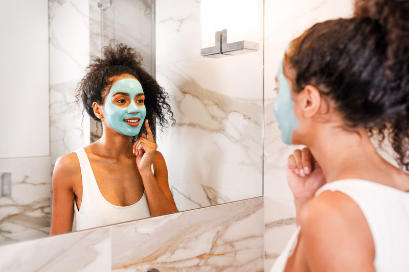 Young Adult Portrait Real People Indoors  Mirror Bathroom Reflection Home Lifestyles Beautiful Woman Preparation  Real Natural Mask Clay Hairstyle Indoors  African American Headshot Adult Cosmetics