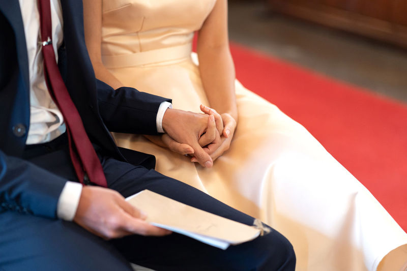 Couple holding hands during church ceremony Women Real People Indoors  Midsection Adult Hand Sitting Well-dressed People Human Hand Men Holding Clothing Focus On Foreground Table Human Body Part Two People Front View Holding Hands Relationship Togetherness Wedding Couple - Relationship Church