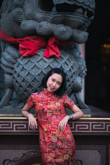 Portrait of smiling young woman standing against built structure