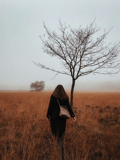 Woman standing in a misty moorland