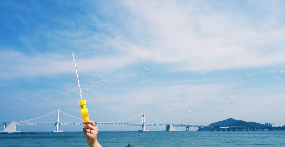 Cropped hand holding bubble wand against gwangandaegyo