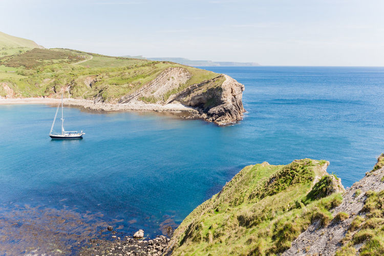 Beach Beauty In Nature Blue Day Horizon Horizon Over Water Idyllic Land Lulworth Cove Nature Nautical Vessel No People Rock Rock - Object Rocky Coastline Sailboat Scenics - Nature Sea Sky Tranquil Scene Tranquility Turquoise Colored Water Yacht