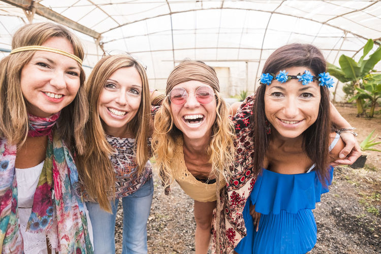 Portrait of smiling friends in greenhouse