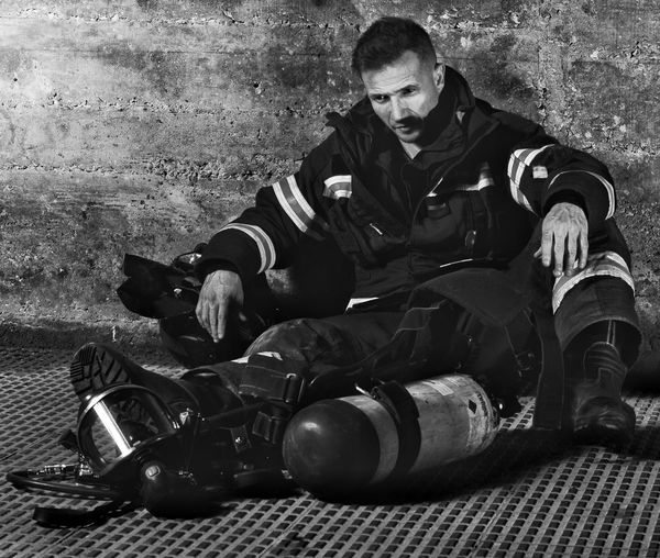Full Length Of Firefighter Sitting Against Wall