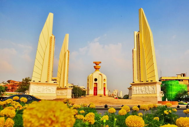 Democracy Monument Roundabout in Bangkok Architecture Bangkok Thailand. Built Structure Circle Constitution Day Democracy Flower History Human Representation Low Angle View Marigold Flower Monument Nature No People Outdoors Polity Rachadumnern Religion Sculpture Sky Spirituality Statue Thailand Yellow