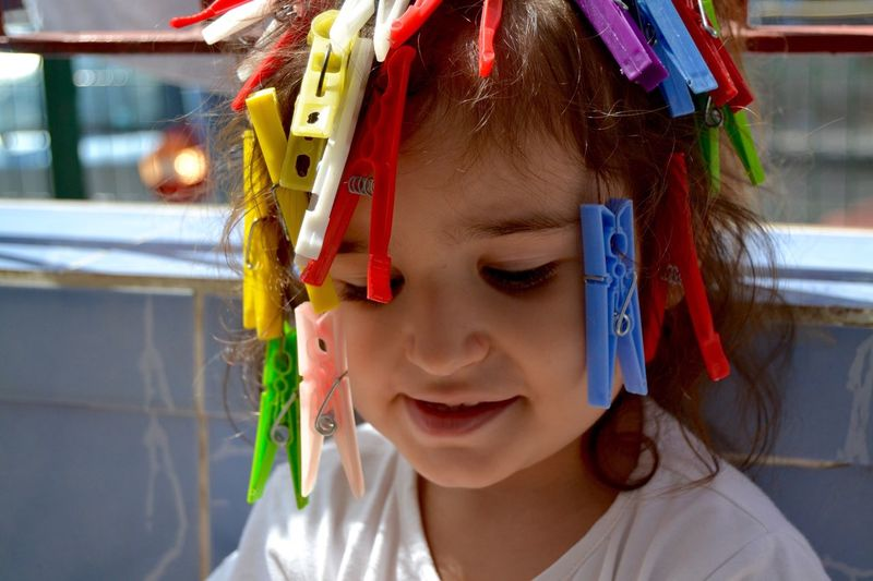 Close-Up Of Girl With Clothespins In Hair