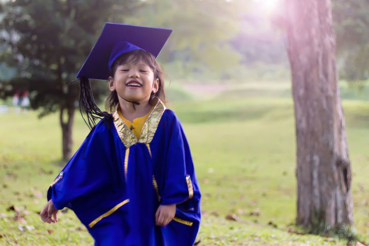 Smiling Girl Wearing Graduation Gown While Standing Outdoors