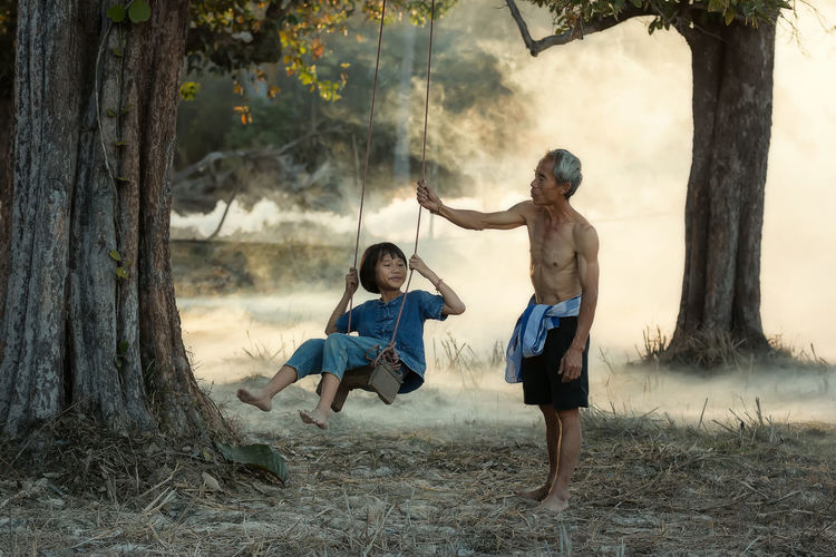 Grandfather Assisting Daughter While Swinging By Tree On Field