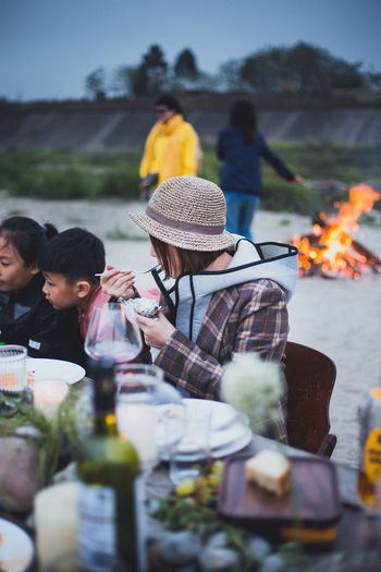 Adult Bonfire Burning Casual Clothing Drink Fire Flame Food Food And Drink Glass Group Of People Hat Heat - Temperature Leisure Activity Lifestyles Men Nature Outdoors People Real People Selective Focus Women