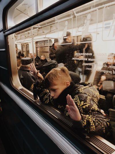 Rear view of boy on railroad station platform seen through train window