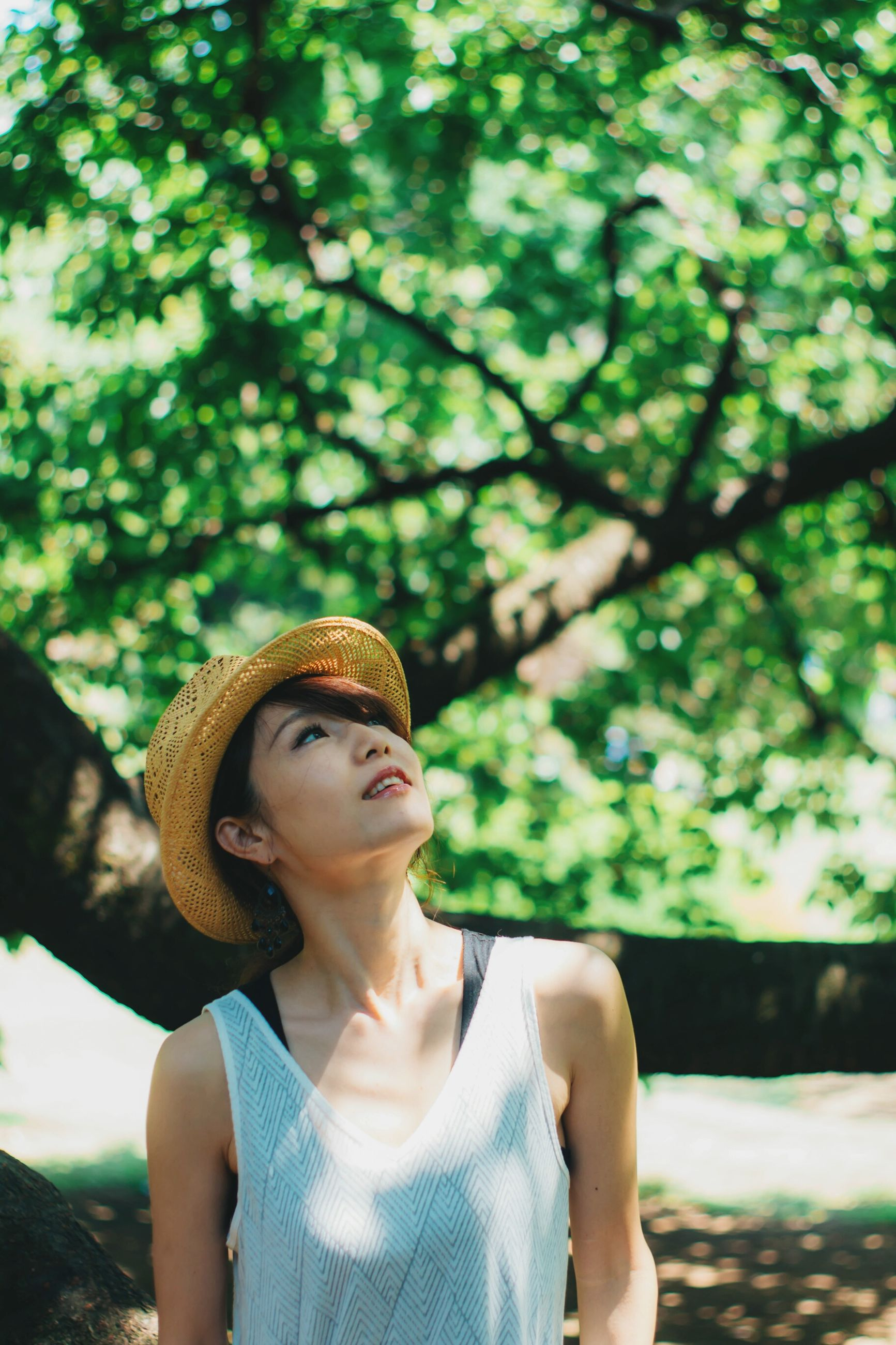 tree, young women, young adult, front view, real people, outdoors, one person, day, nature, leisure activity, lifestyles, focus on foreground, beautiful woman, portrait, beauty in nature, close-up