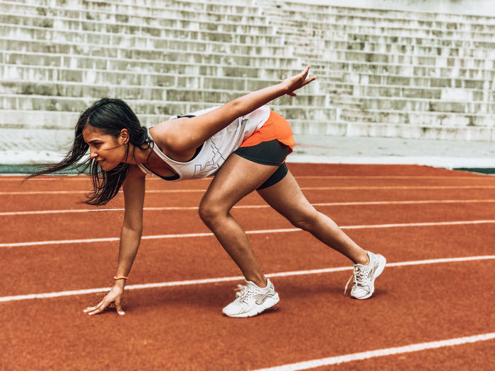 Side view of woman exercising on sports track