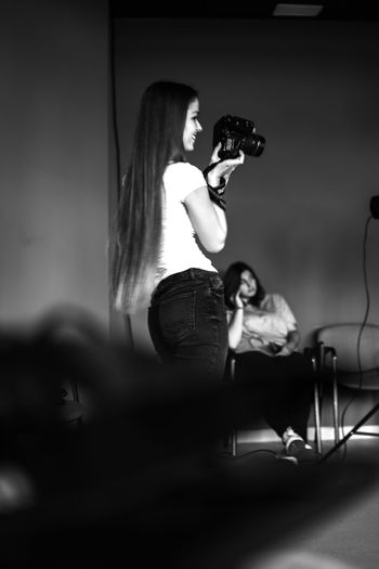 Young woman photographing while sitting on stage