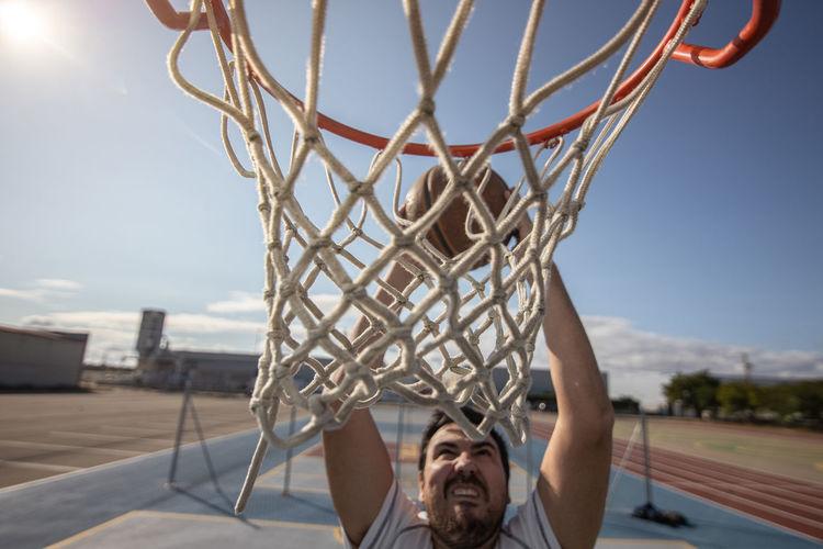 Portrait of basketball hoop against sky