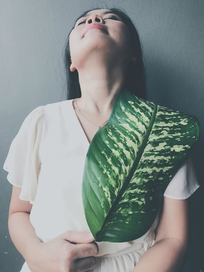 Young Woman With Green Leaf Standing Against Wall